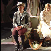 Two children, played by adult actors, sit by a basket of flower petals.