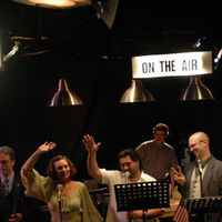 The cast of Strawdog's Wireless 4, with Applause and On The Air signs lit above.
