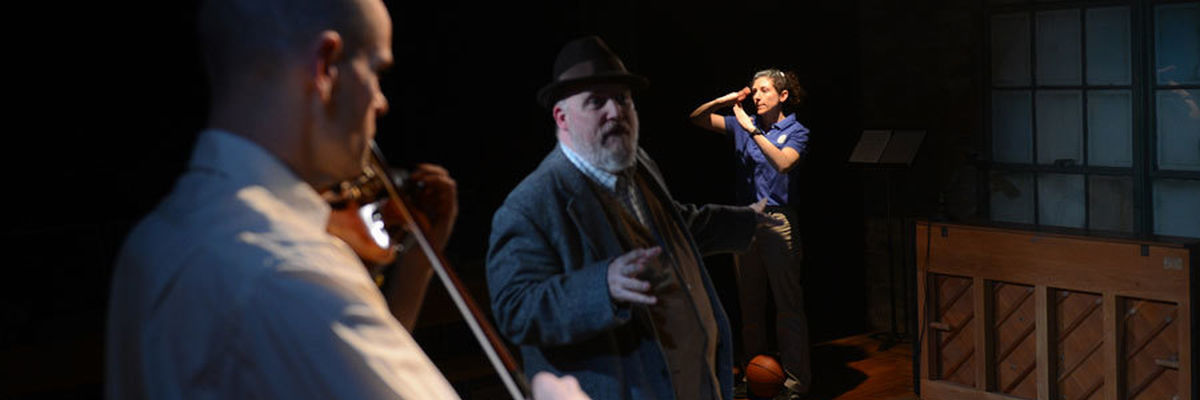 In the foreground, a violinist, in the background, a basketball coach, and in between, ensemble member Jamie Vann.